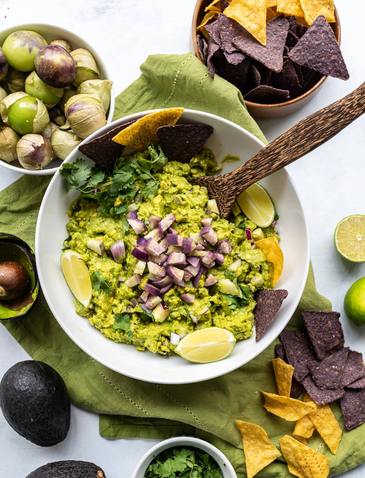 white bowl of tomatillo guacamole with green avocados and purple tomatillos lime slices blue and yellow chips