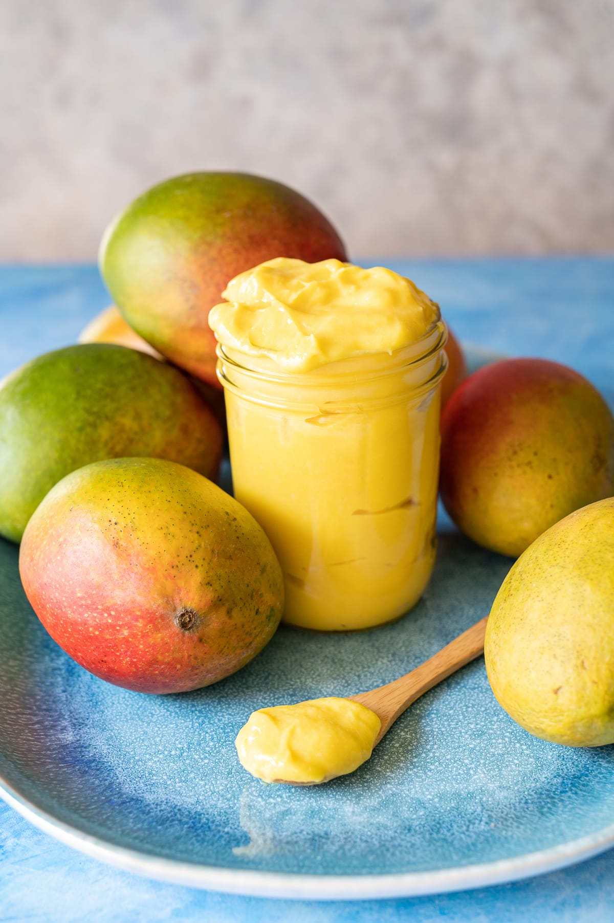 yellow mango curd in a jar on a blue plate with whole mangoes