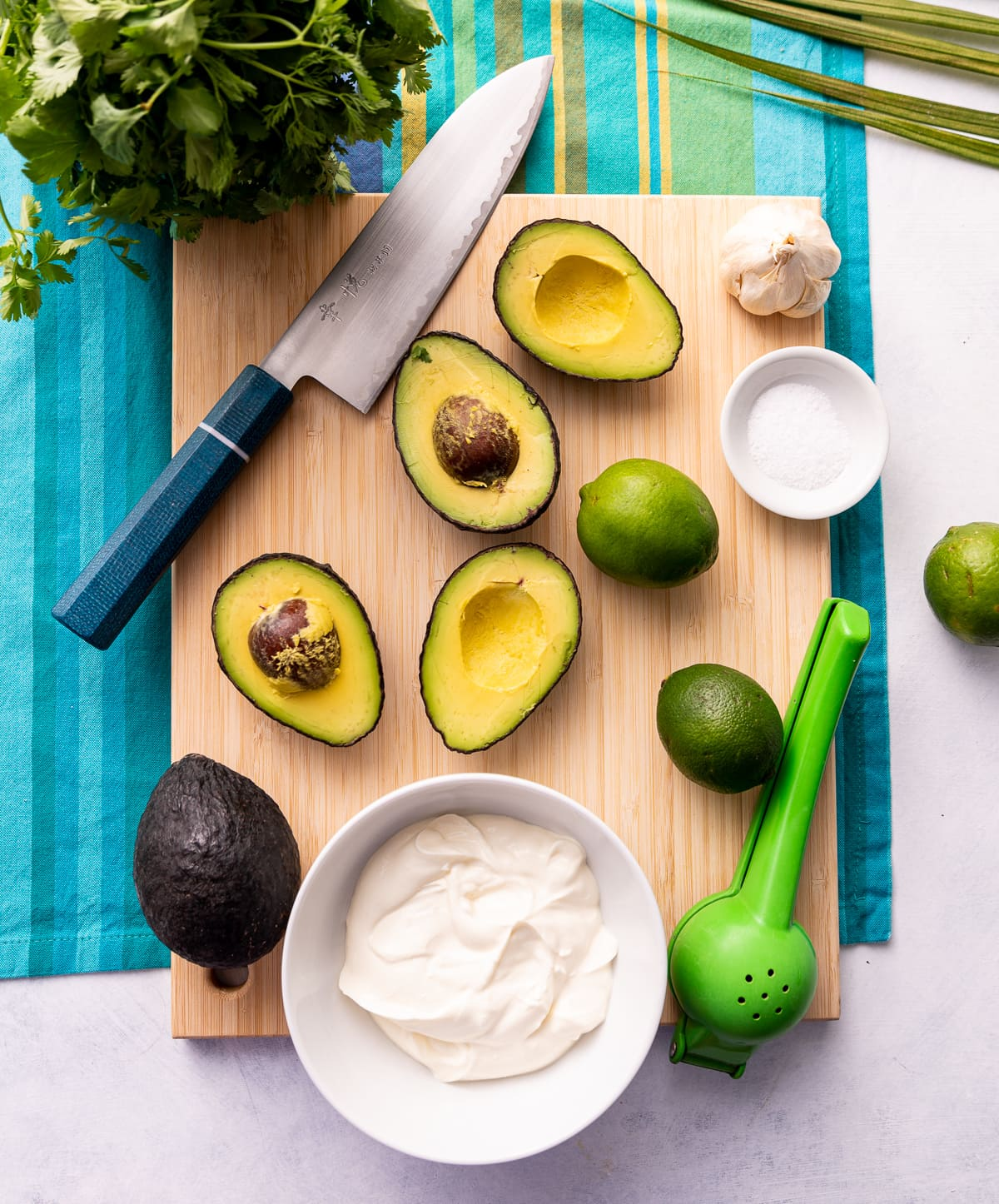 cutting board with avocados sliced in half whole limes knife with blue handle bowl of white sour cream green citrus press