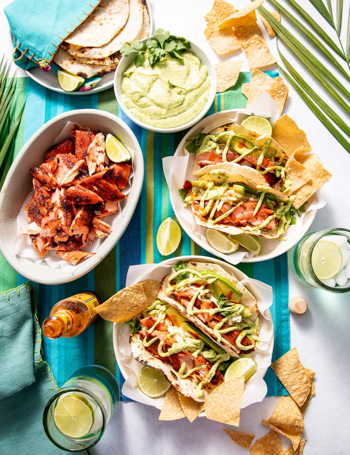 smoked salmon tacos in white bowls with chips smoked salmon a bowl green avocado crema in a white bowl plate of tortillas