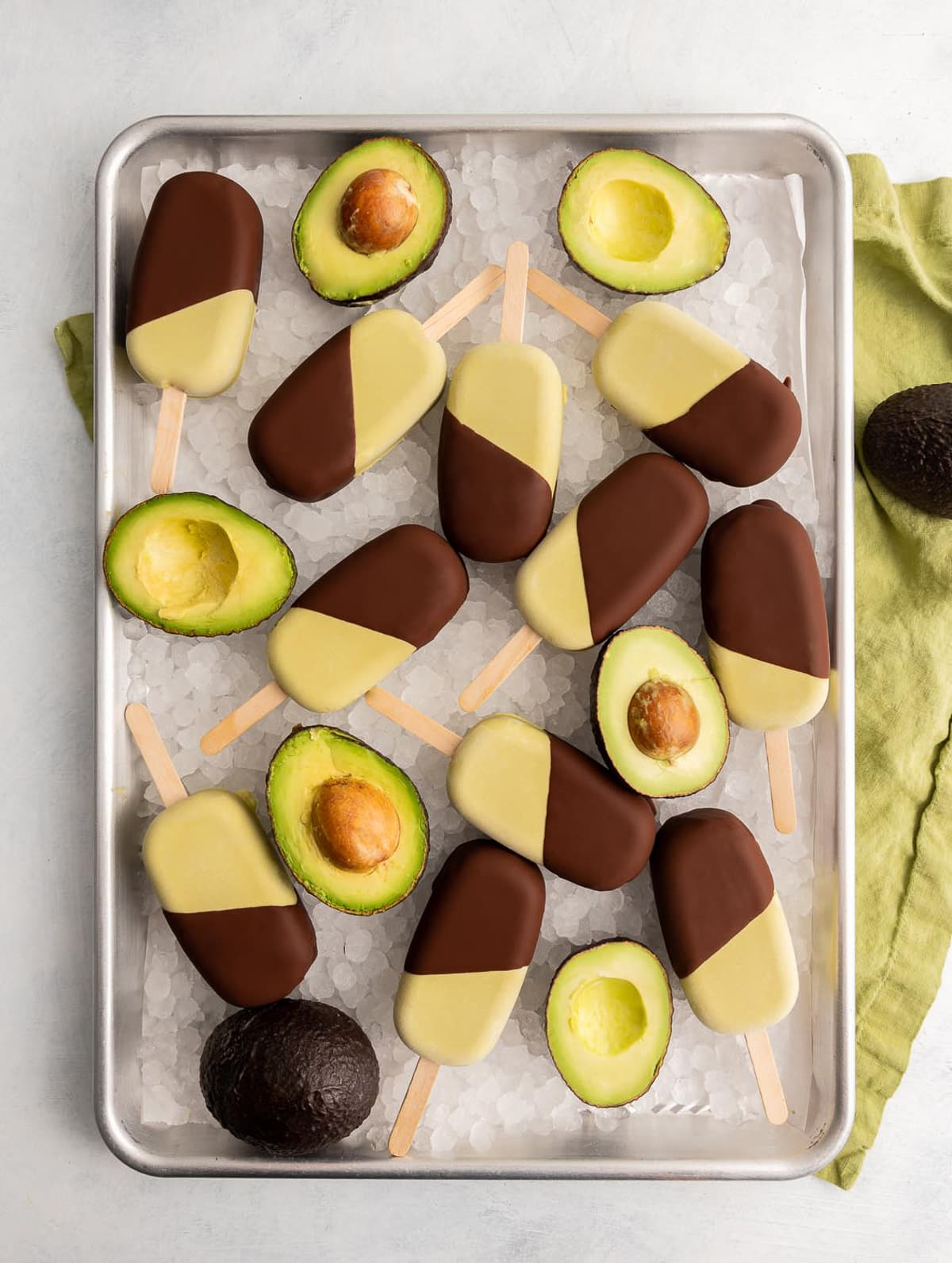 tray of ice with green avocado ice cream bars half dipped in chocolate on the ice with avocados cut in half