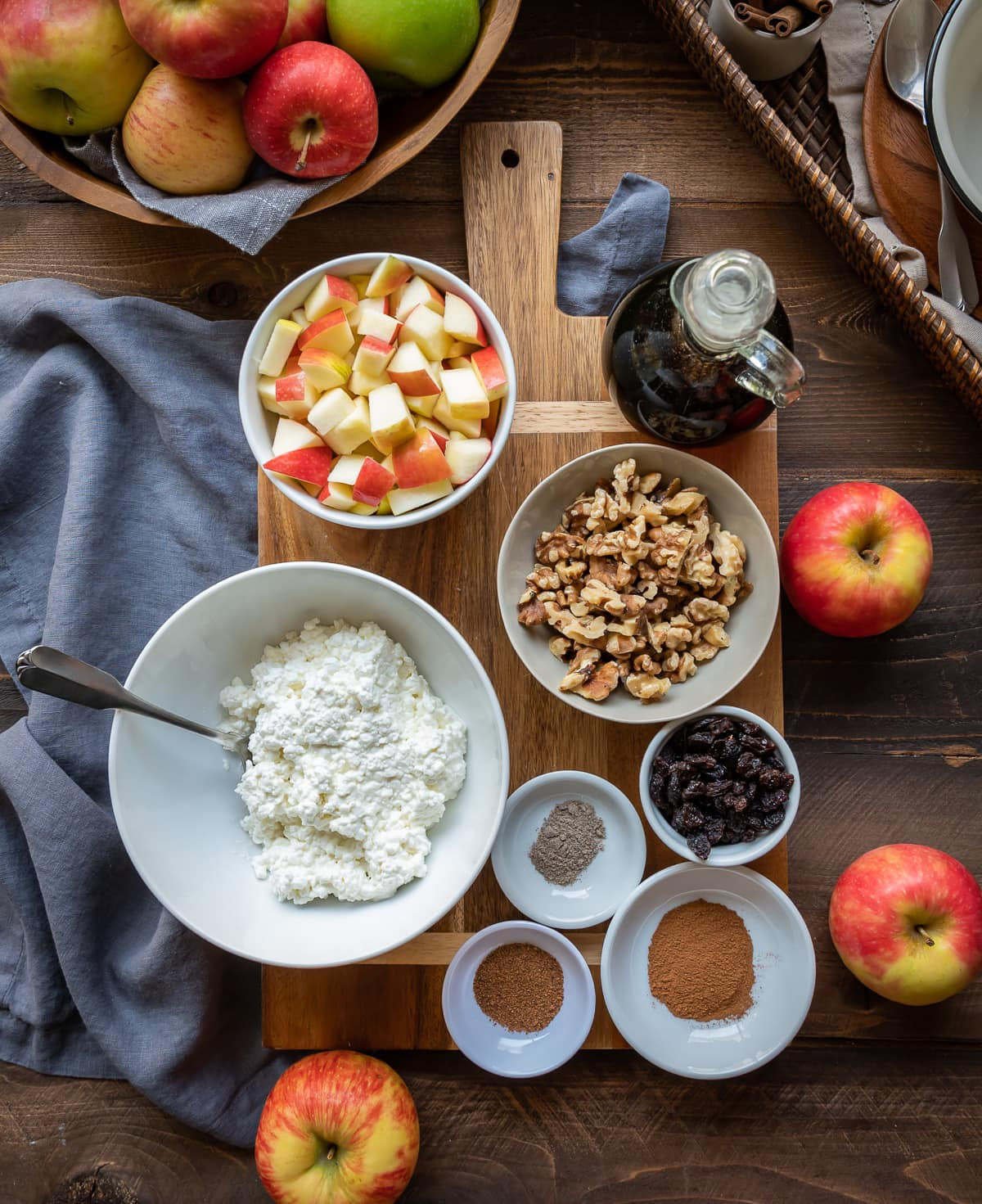 brown cutting board with bowls filled with ingredients for maple apple cinnamon cottage cheese breakfast bowls bowl of cottage cheese bowl of apples bowl of nuts small bowls of spices whole apples