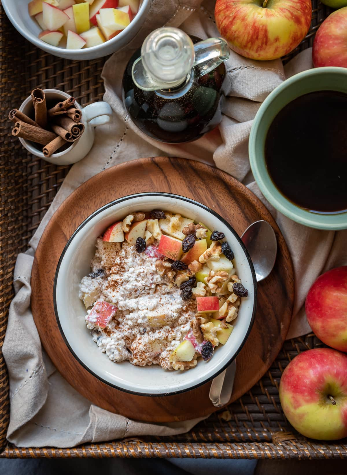 brown basket with apples cup of tea cup with cinnamon sticks cinnamon white bowl on brown plate filled with apple cottage cheese breakfast bowl