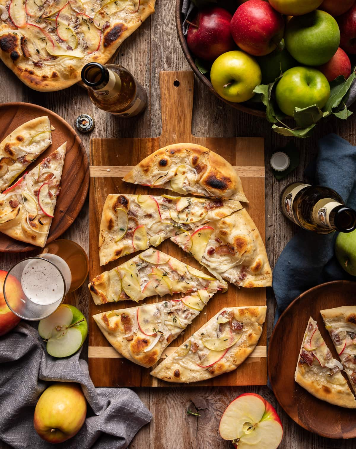 flammkuchen flatbread with apples onion and bacon cut into slices on on a cutting board with whole apples and bottles of german beer