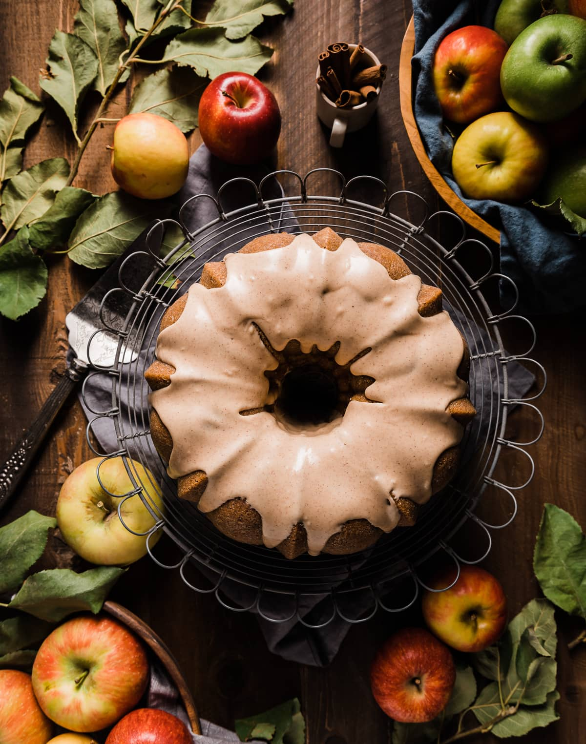 brown sugar bundt cake with cinnamon icing on a wire cake plate with whole yellow red and green apples grey napkin