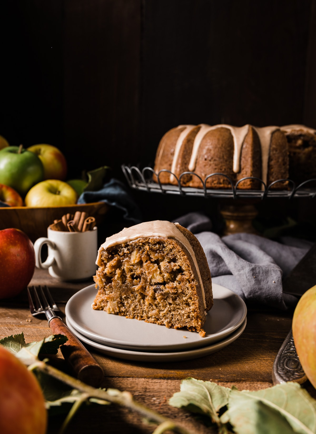 slice of brown sugar bundt cake on a grey cake plate with whole cake in back on a wire cooling rack bowl of apples bowl of cinnamon sticks