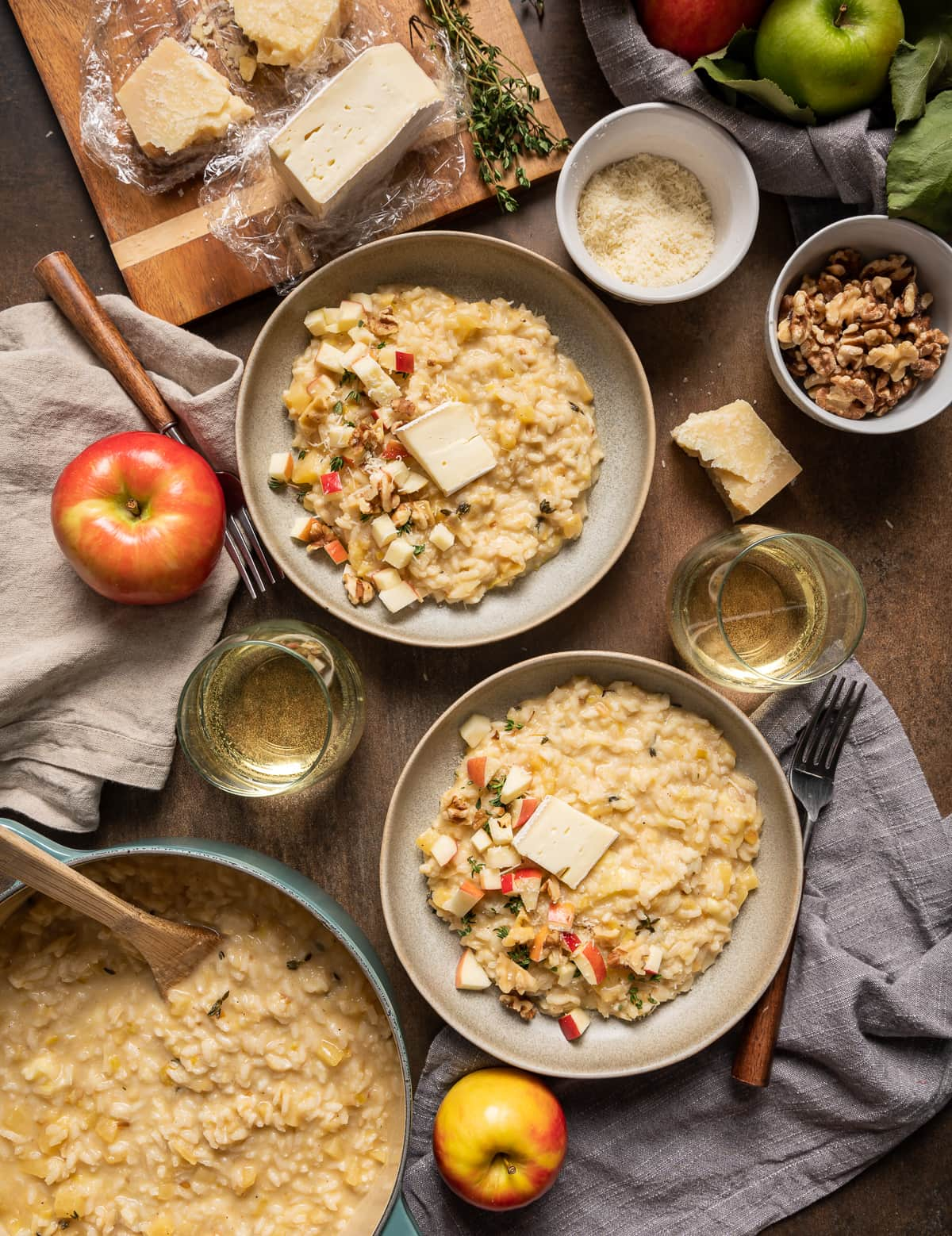 bowls of brie risotto with apples and walnuts glasses of wine pot of brie risotto whole apples cutting board with brie and parmesan cheese