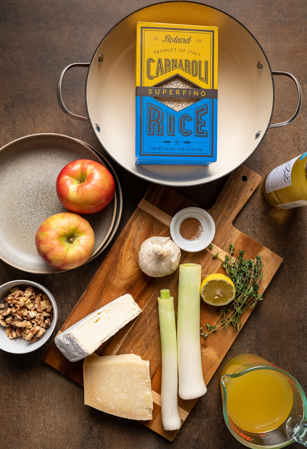preparation ingredients for making risotto with box of carnaroli rice leeks apples cheese garlic lemon thyme wine broth