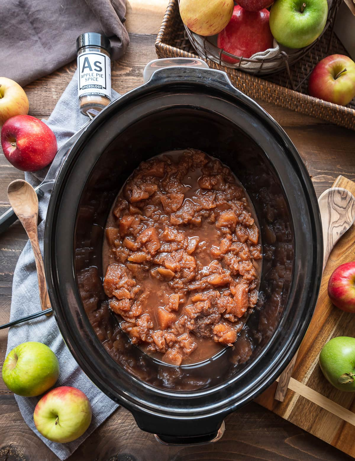 cooked apples in a slow cooker jar of spice whole apples with apples in a basket