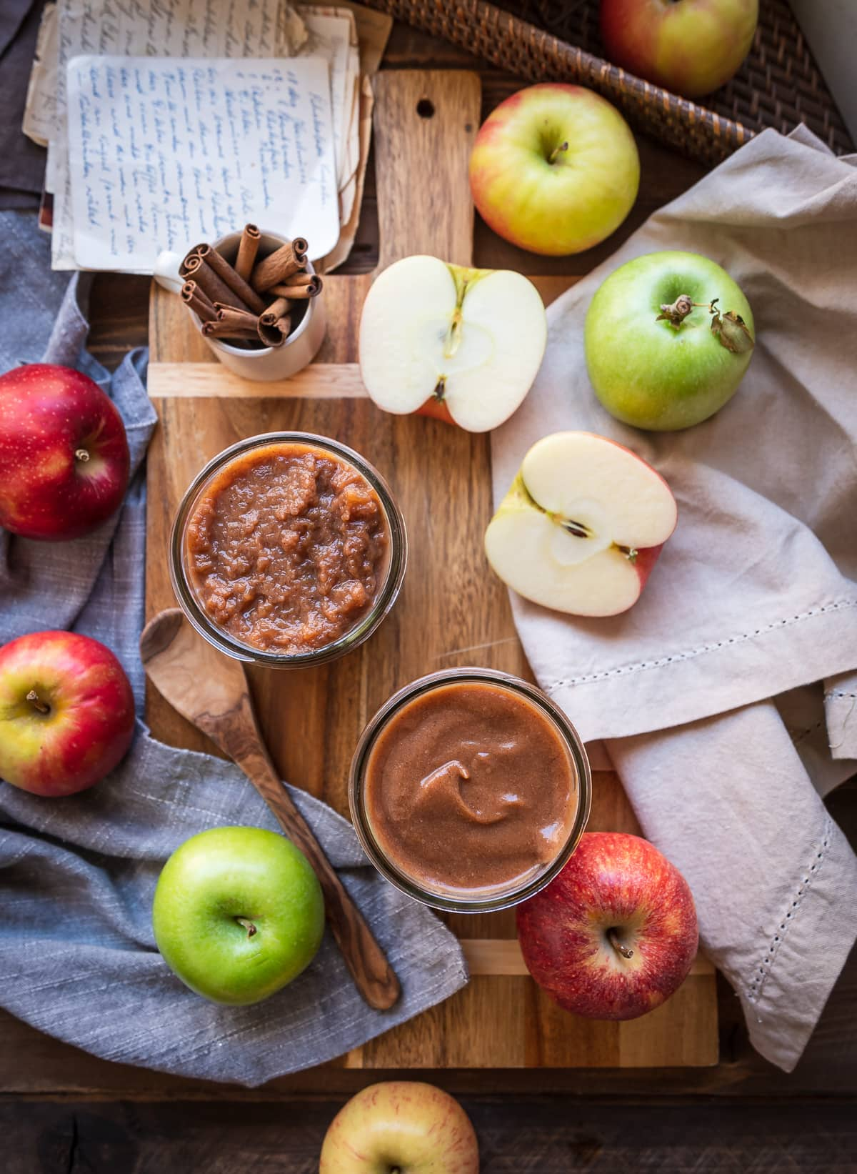 caramel brown slow cooker apple butter in jars whole apples napkins spoon whole cinnamon sticks