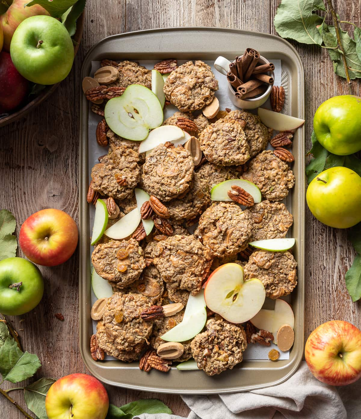 apple oatmeal cookies on a tray with pecans apple slices golden raisins and whole red and green apples